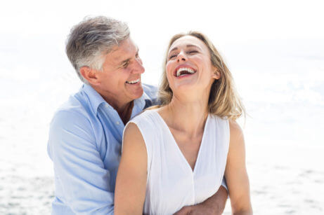 S-partnerem-1-happy-couple-laughing-together-beach-267650246-461x307